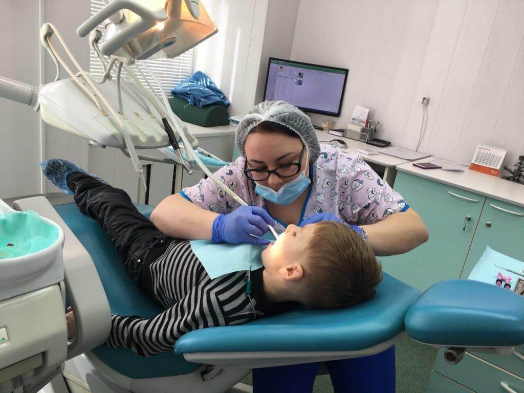 врач стоматолог удаляет кариес ребенку